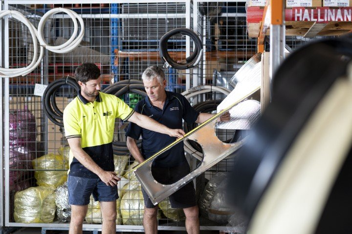 Don Hallinan and apprentice assessing air conditioning equipment
